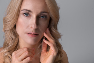 Perfection. Close-up portrait of gorgeous graceful middle-aged naked woman is looking at camera pensively while touching her face with tenderness. Isolated background. Copy space