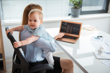Full length portrait of cheerful baby hugging mother in office. Female typing in keypad of laptop while locating at table in office. Job and family concept