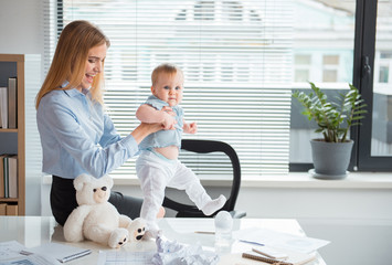 Side view smiling woman holding glad kid. Girl learning to go on desk in office. Occupation, family and balance concept