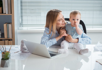 Portrait of smiling mother telling with calm kid. He keeping finger in mouth while locating on desk. Occupation and family concept