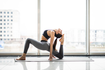Young pretty woman practicing yoga asana in panoramic windows background