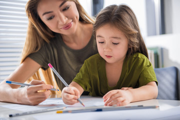 Portrait of joyful girl drawing picture with her mother with interest. She is holding pink pencil while sitting at table at home