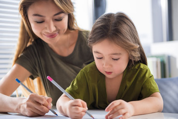 Portrait of interested asian girl painting image with her mother. They are holding colorful pencils with joy