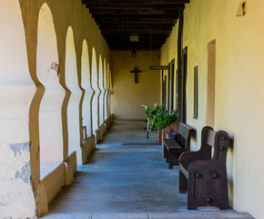 outside arched walkway with wooden benches at a California mission