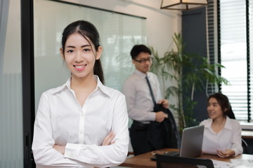Portrait of confident young Asian business woman standing in the office with colleagues in meeting room background.