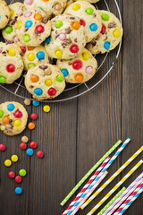 Children's cookies with colorful chocolate sweets in sugar glaze on a brown wooden background. Selective focus. Top view. Place for text.