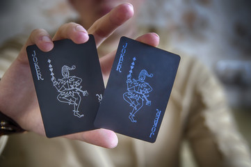 A man holds in his hands two playing cards