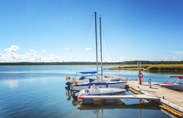small boats and yachts on a pier on a summer lake. Beautiful landscape