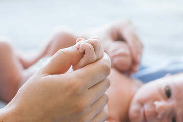 cute newborn baby hold mother by the thumb. happy motherhood. family values.