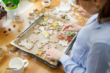 Woman in kitchen making Christmas gingerbread cookies