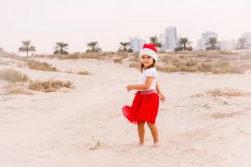 Cute little girl wearing Christmas hat in the desert