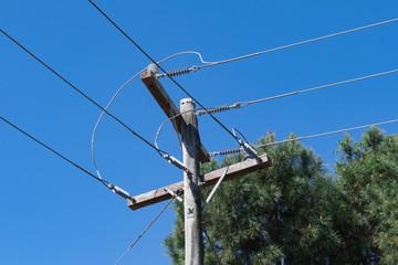 Strommast mit Blickrichtung Himmel und einem Baum im Hintergrund