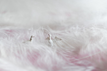 Pair of gooses sitting in a pile of feathers - miniature figures