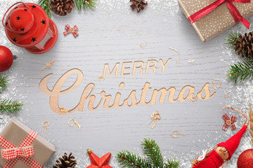 Merry Christmas text carved in a wooden surface and surrounded by Christmas decorations. Christmas tree, gifts, balls, lantern, pinecones and doll.