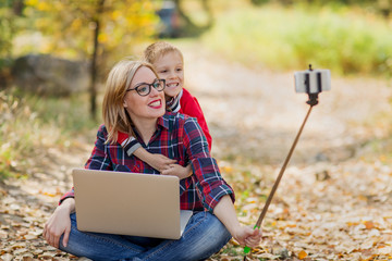 Mom and the boy take pictures of themselves on the smartphone, smiling happily at the camera. Mom holds a laptop on his lap, and his son hugged her from behind,  a very fuzzy autumnal background