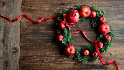 Pomegranate,apples and fir leaves.Christmas wreath.dark wooden background