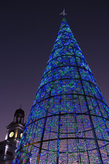 Madrid - An artificial Christmas tree illuminates 2017 in Puerta del Sol square and Clock Tower in background.