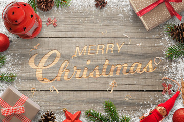 Creative hand carved Merry Christmas text in a wooden surface. Surrounded with Christmas decorations. Top view of branches, gifts, balls, lantern, pinecones and doll.