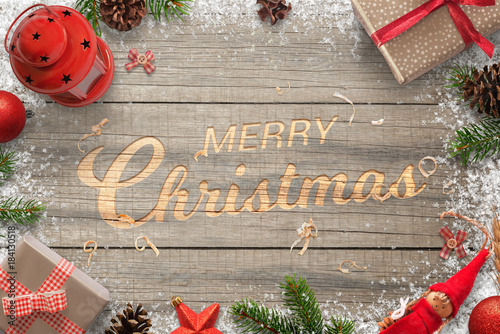 Creative hand carved merry christmas text in a wooden surface