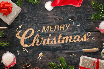 Merry Christmas greeting carved into a wooden surface. Christmas gifts, tree branches, chisel, candles, pinecones and Santa Claus hat beside.