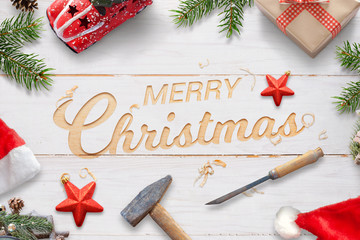 Creative Chrtistmas greeting with carved text on white wooden surface with hammer and chisel. Christmas decorations beside.