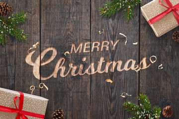 Christmas greeting text hand carved on dark wooden surface with Christmas decorations. Gifts, fir branches and pinecones beside.