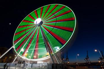 "GENOA, ITALY, NOVEMBER 27, 2017 - Ferris wheel with colored lights in ""Porto Antico"" harbor zone in Genoa, Italy"