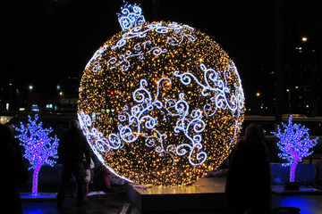 A huge New Year's glowing ball in motley garlands on the city street