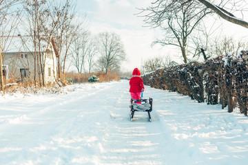 Little girl walking on winter sunny day