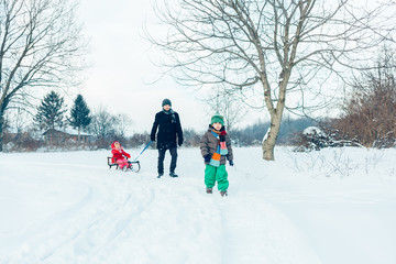 Dad walking with their children in the snow