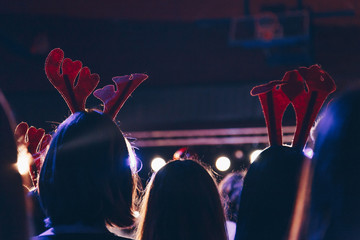 rear view of audience wearing christmas deer horns at a christmas concert. silhouettes of concert...