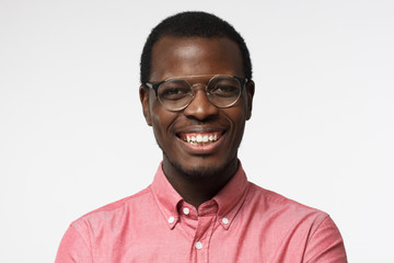 Closeup shot of young African male in round spectacles pictured isolated on white background wearing casual clothes, showing toothy open smile, looking positive and confident, satisfied with life