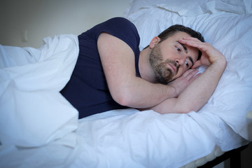 Sad and upset man trying to sleep in bed
