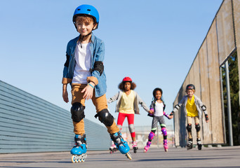 Schoolboy in helmet rollerblading with his friends