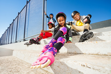 Girl in roller skates sitting with friends