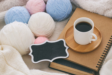 Cup of coffee on the old book and empty chalkboard over cozy and white blanket. Top view.