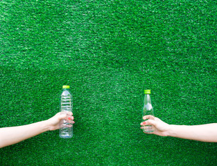Hand hold show Recyclable plastic bottle a glass of water green background