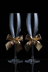 Festive champagne glasses with golden bows on a glass table