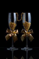 Festive champagne glasses with golden bows and beads on a glass table