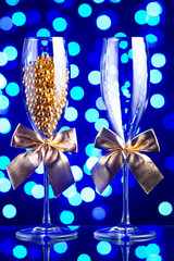 Festive champagne glasses with golden bows and beads on a glass table with a beautiful blue bokeh