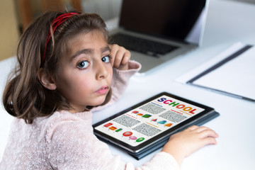 education concept. Little girl at home with school geometry work on the tablet / girl student with her tablet computer reading the school work