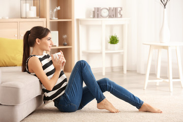 Young woman with cup of tea sitting on carpet near sofa at home