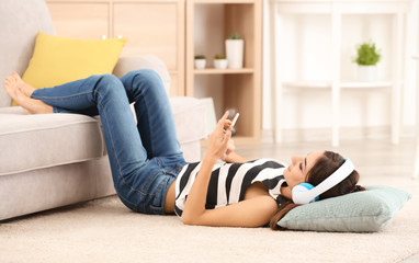 Young woman listening to music through headphones on carpet near sofa at home