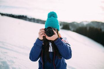 the girl is taking pictures in the winter