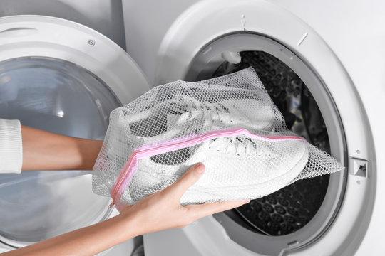 Woman putting mesh with white sneakers into washing machine, closeup