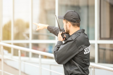 Male security guard using portable radio transmitter near building outdoors Wall mural