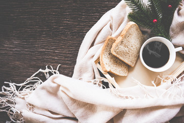 Cup of coffee on rustic wooden serving tray in the cozy bed with blanket. Knitting warm woolen sweater in the winter weekend, top view, vintage tone, Lifestyle Concept.