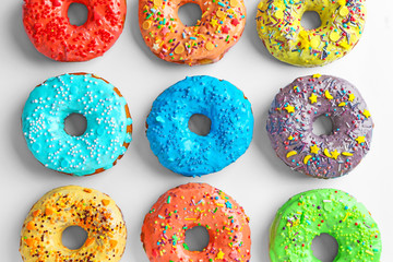 Tasty colorful donuts on white background