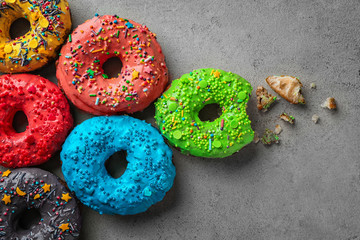 Colorful donuts with sprinkles on grey background