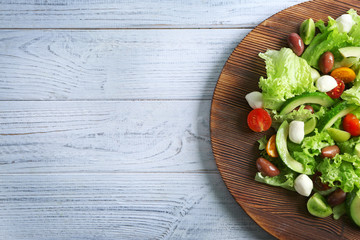 Fototapeta Board with delicious vegetable salad on wooden background